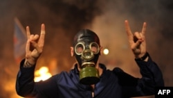 Истанбулнинг Кадиқўй туманидаги намойишчи полиция кўздан ёш чиқарувчи газ қўллаши мумкинлигини эсга олган ҳолда противогаз кийиб олган.