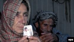 Родители Шафката Хуссейна, пакистанца, приговоренного к смертной казни, с его фотографией.