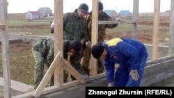Мужчины строят дом. Иллюстративное фото. Актобе, 14 апреля 2013 года.