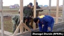Участники строительства устанавливают деревянный каркас. Село Акшат.