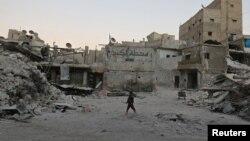 Алеппо қаласындағы шабуылдан қираған үйлердің жанынан өтіп бара жатқан бала. 29 қыркүйек 2016 жыл. (Көрнекі сурет.)
