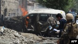 Afghan security forces inspects a damaged vehicle at the site of a suicide bombing attack that targeted NATO forces in Kabul on July 7.