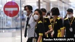 خدمه شرکت هواپیمایی سنگاپوری اسکوت در حال بازگشت از سفر در فرودگاه چانگی