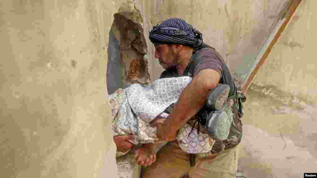A Free Syrian Army fighter carries the body of a fellow fighter during clashes in Aleppo, Syria. (Reuters/Goran Tomasevic )