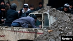 Syria -- A man looks for survivors inside a pick-up truck at a damaged site after what activists said was an airstrike by government forces in Duma, Damascus, December 15, 2013