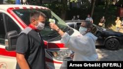 Medicinska sestra mjeri temperaturu pacijentima ispred bolnice u Doboju u Bosni i Hercegovini