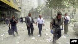 Люди йдуть по вулиці поруч із зруйнованими вежами Всесвітнього торгового центру в Нью-Йорку, 11 вересня 2001 року