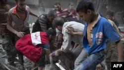 Syrians surround a man as he cries over the body of his child after she was pulled out from the rubble of a building following government air strikes in the rebel-held neighborhood of Al-Shaar in Aleppo on September 27.