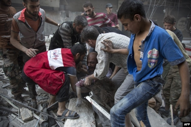 Syrians surround a man as he cries over the body of his child after she was pulled from the rubble of a building following air strikes by government forces in the rebel-held neighborhood of Al-Shaar in Aleppo on September 27.