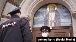 Сотрудники полиции в защитных масках у церкви. Иллюстративное фото.