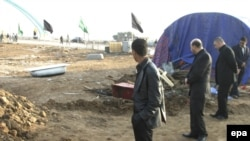 Iraqis inspect the site of the suicide attack on February 1 that killed more than 40 people.