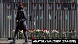 Një grua me maskë mbrojtëse ec në rrugët e qytetit Shën Petersburg në Rusi.