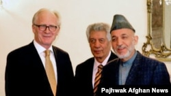 """UN envoy Kai Eide (left) has called on Afghan President Hamid Karzai's next government """"should be composed of competent, reform-oriented personalities that can implement a reform agenda."""""""