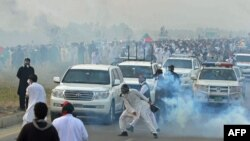 Activists of opposition party Pakistan Tehreek-e Insaf (PTI) clash with police during a march to the capital, near the northwestern city of Swabi on October 31.