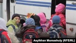 Школьники заходят в автобус. Алматинская область, 3 апреля 2013 года. Иллюстративное фото.