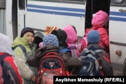 Автобусқа мініп жатқан мектеп оқушылары. Алматы облысы, 3 сәуір 2013 жыл. (Көрнекі сурет)