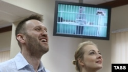 Russian opposition leader Aleksei Navalny and his wife, Yulia, laugh during a video-link with his brother Oleg, shown on a screen, in a court in Moscow on February 17.