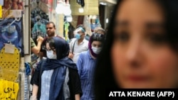 Iran -- Iranians, some wearing protective gear amid the COVID-19 pandemic, shop at the Tajrish Bazaar market in the capital Tehran on July 14, 2020. (Photo by ATTA KENARE / AFP)