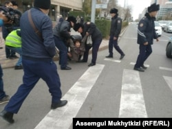 Police in Nur-Sultan detain a woman who was trying to gather for an anti-government demonstration.