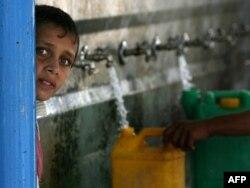 Палестинцы наполняют бутылки и контейнеры водой в штаб-квартире Агентства ООН для помощи и организации работ (БАПОР) в лагере беженцев Хан-Юнис на юге Сектора Газа, 27 октября 2009 года