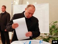"""Владимир Путин опускает свою бюллетень в КОИБ – """"Комплекс обработки избирательных бюллетеней"""""""