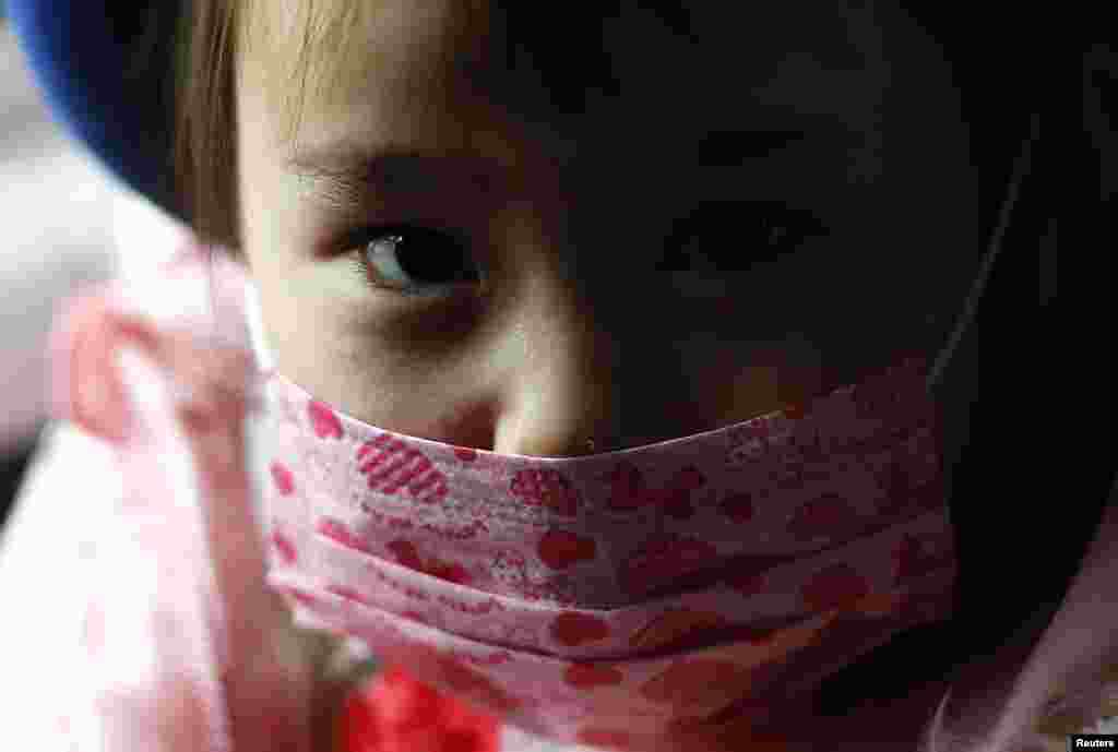 A girl wears a mask as she rides a school bus.