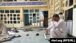A man sits in a Herat mosque the day after a deadly attack that left at least 33 people dead.