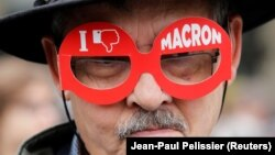 Французский избиратель в очках с надписью «Я не люблю Макрона»