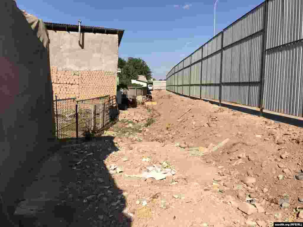 Территория, за которой ведется строительство, огорожена высоким забором.