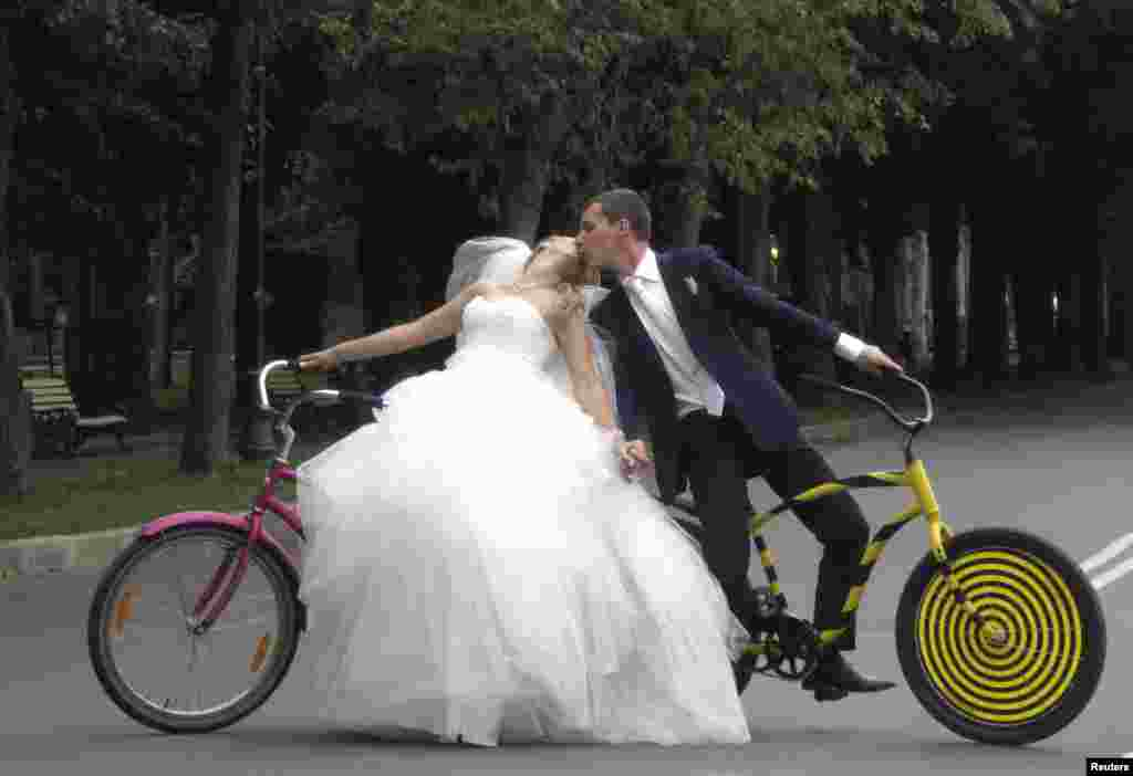 Yelena Babkini (left) and her husband, Boris, kiss as they ride through Gorky Park on bicycles after having been married earlier in the day in Moscow. (Reuters/Gary Hershorn)