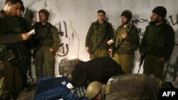 Israeli soldiers and an Ultra Orthodox man pray at Joseph's Tomb in the Palestinian town of Nablus, where an ultra-Orthodox Jew was shot dead on April 24