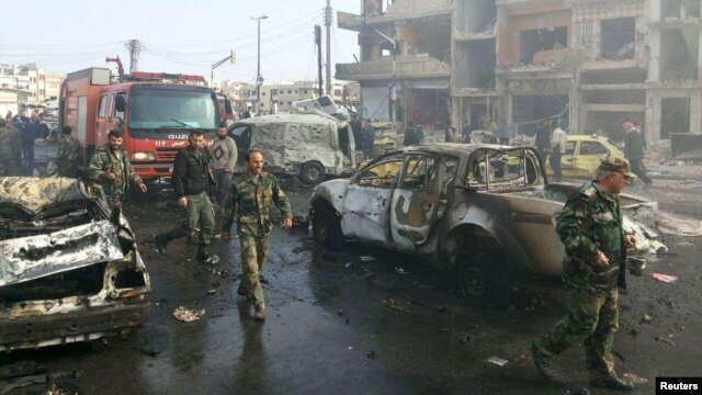 Syrian soldiers inspect the site of two bomb blasts in the government-controlled city of Homs on February 21.
