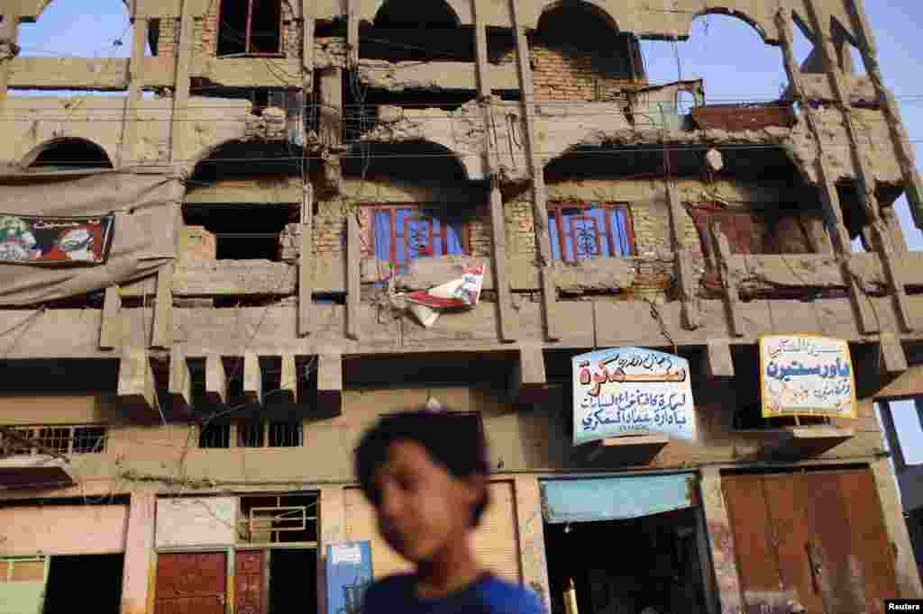 A boy walks past a building in Sadr City, damaged during the 2003 U.S. invasion that toppled Iraqi President Saddam Hussein.