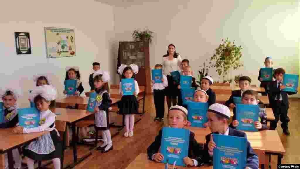 Дети в классе держат в руках учебник казахского языка.