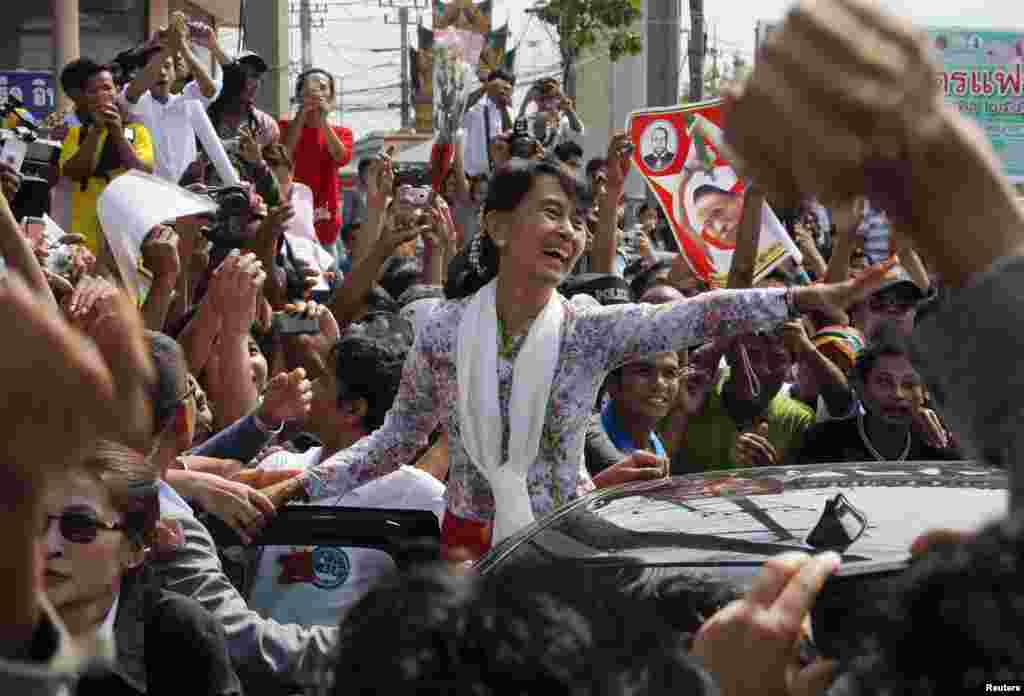 Myanmar's pro-democracy leader Aung San Suu Kyi greets migrant workers from her country while on a visit to Thailand on May 30. (Reuters/Sukree Sukplang)