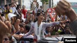 Myanmar's pro-democracy leader Aung San Suu Kyi greets migrant workers from Myanmar in Thailand.