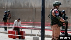 Маж со куфери поминува покрај руски војници во сирискиот град Хомс.