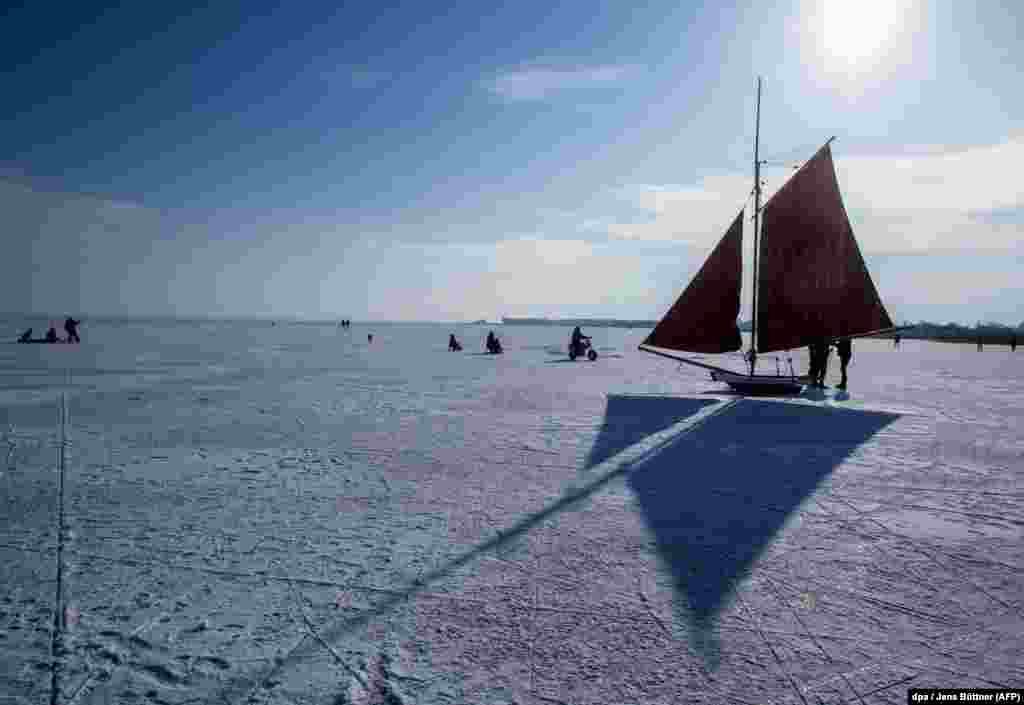 People use traditional iceboats on a frozen lagoon near Ahrenshoop in northern Germany. (AFP/dpa/Jens Buttner)