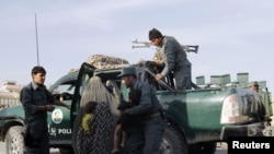Afghan policemen rescue civilians from the site of an attack in Kandahar on October 27.