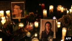Candles surround portraits of federal judge John Roll, who was killed in the attack, and Arizona Representative Gabrielle Giffords, who were shot in the Tuscon, Arizona, rampage.