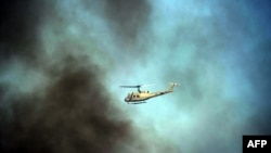 Pakistan -- A security survilience helicopter patrols through smoke clouds during an anti-US demonstration against an anti-Islam film in Islamabad, 21ASep2012