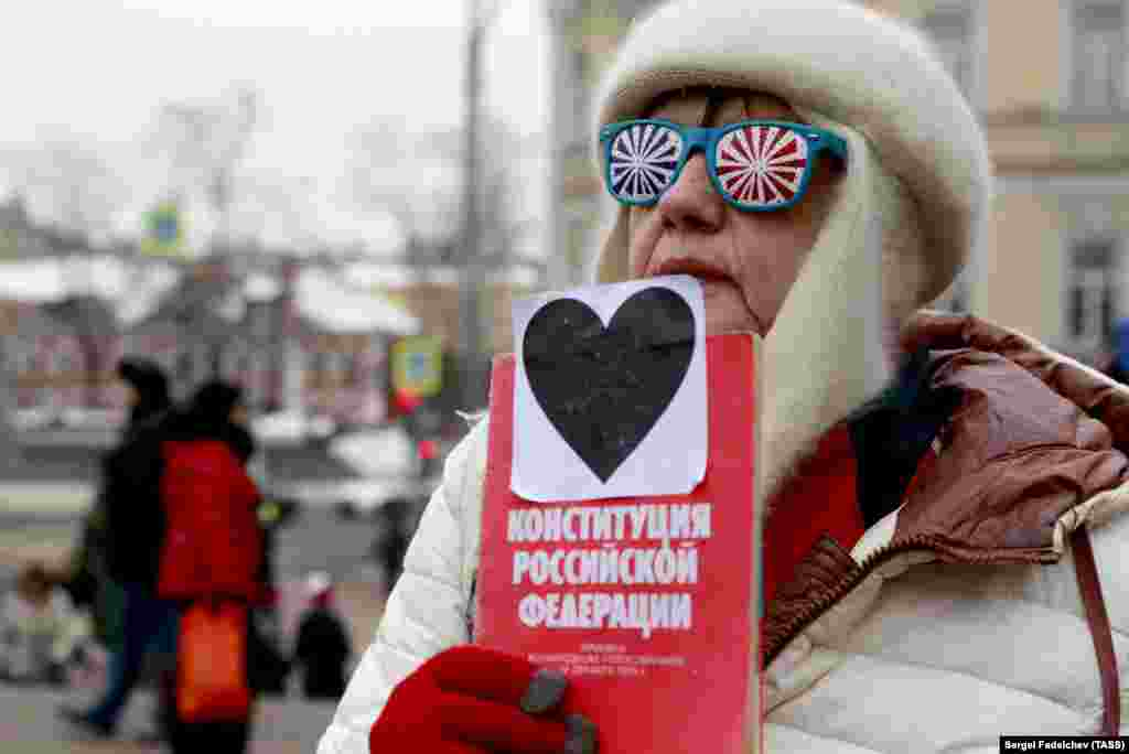 An elderly woman holds a copy of the Russian Constitution as she takes part in the March of Maternal Anger in Moscow on February 10. (TASS/Sergei Fadeichev)