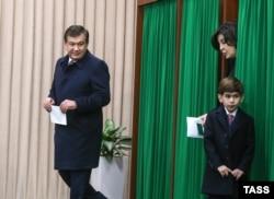 Шаўкат Мірзіёеў з жонкай Зіраатхон і ўнукам на выбарчым участку, сьнежань 2016 г.