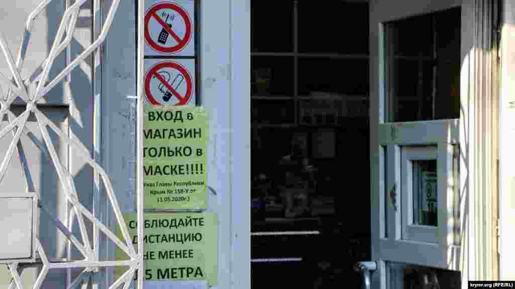 Напоминание о соблюдении мер безопасности из-за пандемии COVID-19 у входа в один из местных магазинов