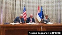 Ambasador Skat, direktor misije USAID-a u Srbiji Majkom de la Rosom i ministarka Joksimović potpisuju sporazum