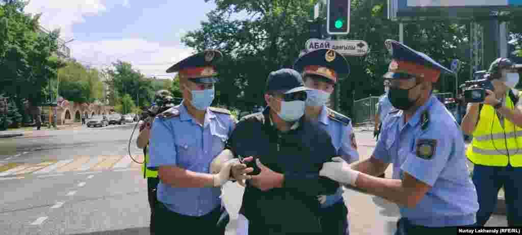 """Полиция Абайдын эстелигинин жанына келген бир нече адамды кармады. Полиция машинеге күчтөп салган адамдардын бири """"Назарбаевдин доору бүттү!"""", """"Қазакстан, алга!"""" деп кыйкырды."""