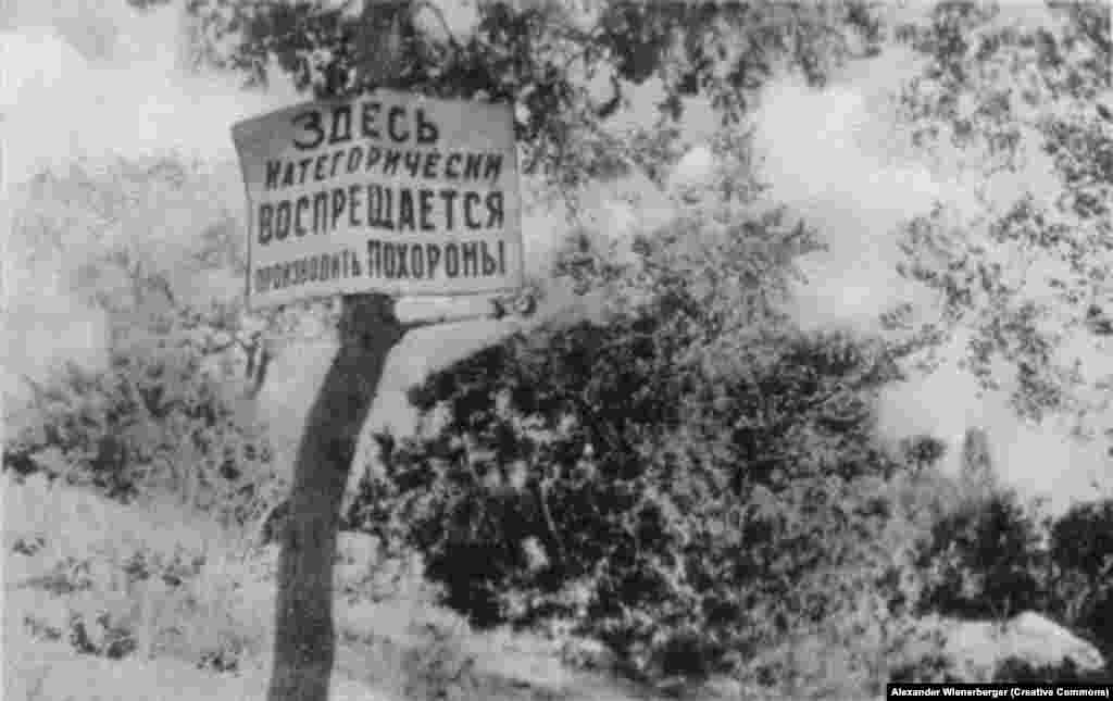 "In the blooming countryside, a sign reads: ""The burial of corpses is strictly forbidden here!"""