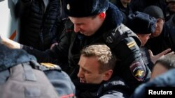 Police detaining Navalny on March 26 in Moscow.