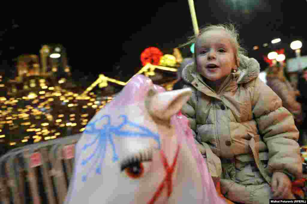 A young girl enjoys the festive atmosphere in Sarajevo before the New Year's holiday. (RFE/RL /Midhit Poturovic)