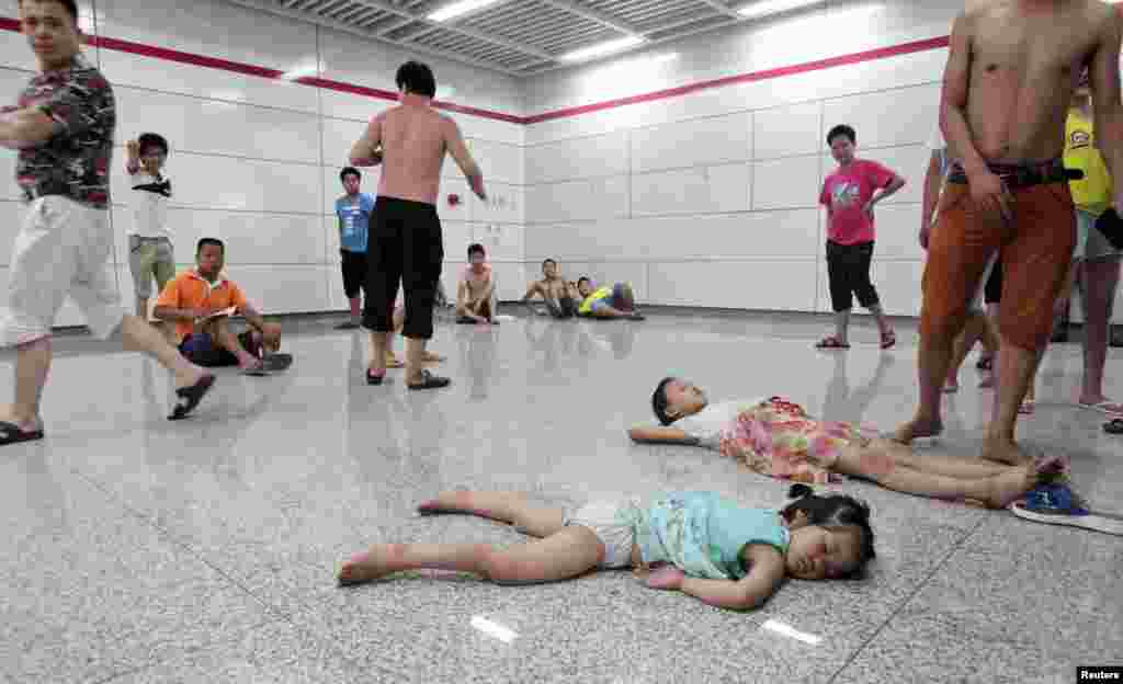 Children sleep on the floor in the relative cool of the Qiaosi subway station in Hangzhou, China on July 25 when the city endured temperatures as high as 40 degrees Celsius.